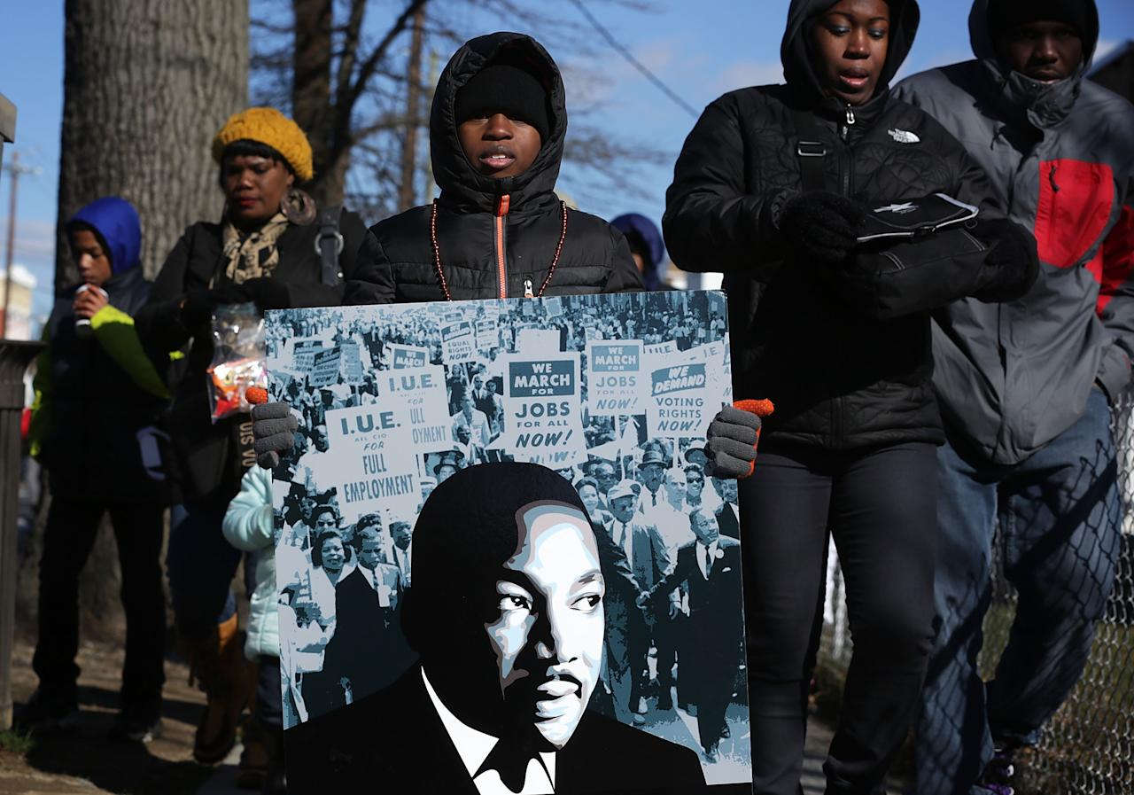 WASHINGTON, DC - JANUARY 18:  Eight-year-old local resident Isaiah Williams holds a portrait of Martin Luther King Jr. during the annual Martin Luther King Holiday Peace Walk and Parade January 18, 2016 in Washington, DC. The nation observes the life and legacy of Martin Luther King Jr. today.  (Photo by Alex Wong/Getty Images)