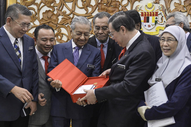 Prime Minister Tun Dr Mahathir Mohamad receives a copy of Budget 2020 from Finance Minister Lim Guan Eng in Parliament October 11, 2019. — Picture by Miera Zulyana