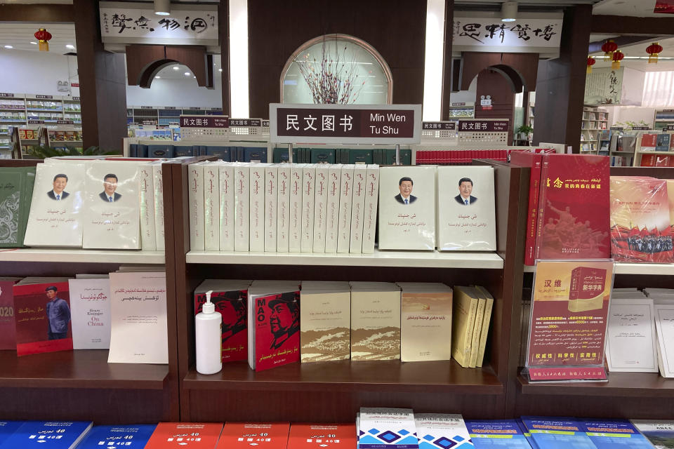 """Uyghur-language copies of writings by Mao Zedong and Chinese President Xi Jinping sit on the shelves of the """"ethnic minority language book"""" section of a bookstore in Aksu, in China's far west Xinjiang region, on March 18, 2021. Four years after Beijing's brutal crackdown on largely Muslim minorities native to Xinjiang, Chinese authorities are dialing back the region's high-tech police state and stepping up tourism. But even as a sense of normality returns, fear remains, hidden but pervasive. (AP Photo/Dake Kang)"""