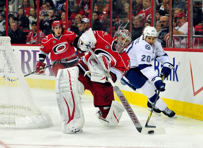 RALEIGH, NC - MARCH 03:  Cam Ward #30 of the Carolina Hurricanes slaps the puck away from Tim Wallace #20 of the Tampa Bay Lightning during play at the RBC Center on March 3, 2012 in Raleigh, North Carolina.  (Photo by Grant Halverson/Getty Images)