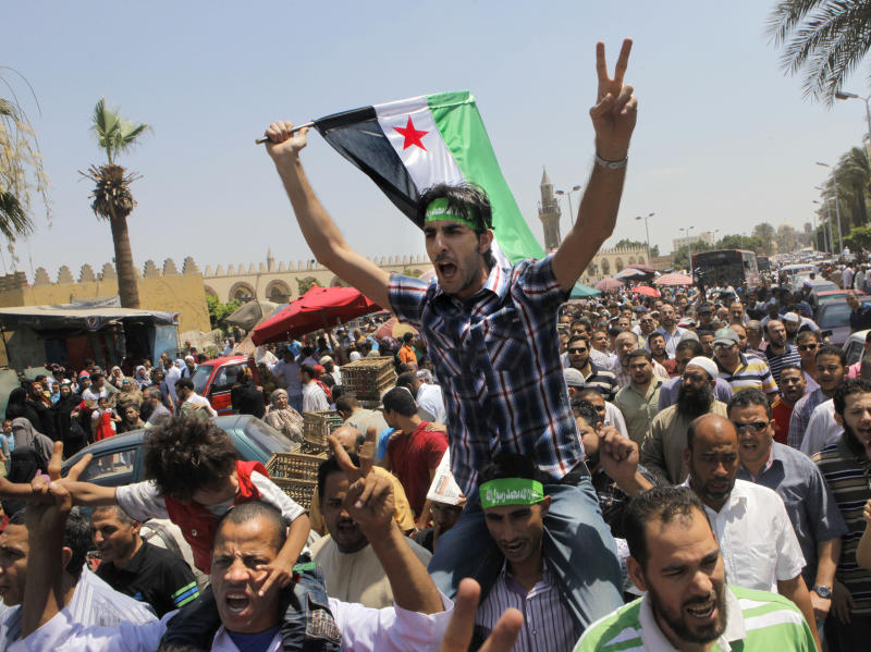 Egyptian Salafis shout slogans against Syrian President Bashar Assad as one waves a Syrian revolutionary flag during a rally after the Friday prayers at Amr Ibn Al As mosque, in Cairo, Egypt, Friday, June 14, 2013. Syrians are being killed at an average rate of 5,000 per month, the United Nation said Thursday as it raised the overall death toll in the civil war to nearly 93,000, with civilians bearing the brunt of the attacks. (AP Photo/Amr Nabil)