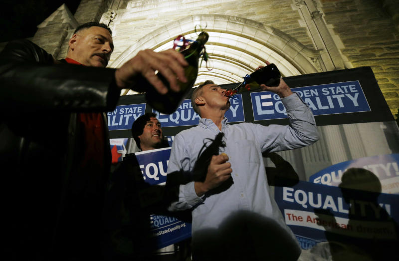 Jonathan Javins, 42, right, of Jersey City, N.J., drinks from a bottle after opening it up to celebrate along with his partner Jack Denelsbeck, 40, center, and Gary Cosgrove, 54, of Lodi, N.J., during a rally at Garden State Equality in Montclair, N.J., hours after a Superior Court Judge ruled that New Jersey is unconstitutionally denying federal benefits to gay couples and must allow them to marry, Friday, Sept. 27, 2013. Judge Mary Jacobson ruled it legal for gay couples to marry in the state beginning Oct. 21, 2013. The ruling comes after a group of gay marriage supporters sued the state in July, days after the U.S. Supreme Court struck down key parts of a law that blocked the federal government from granting benefits to gay couples. (AP Photo/Julio Cortez)