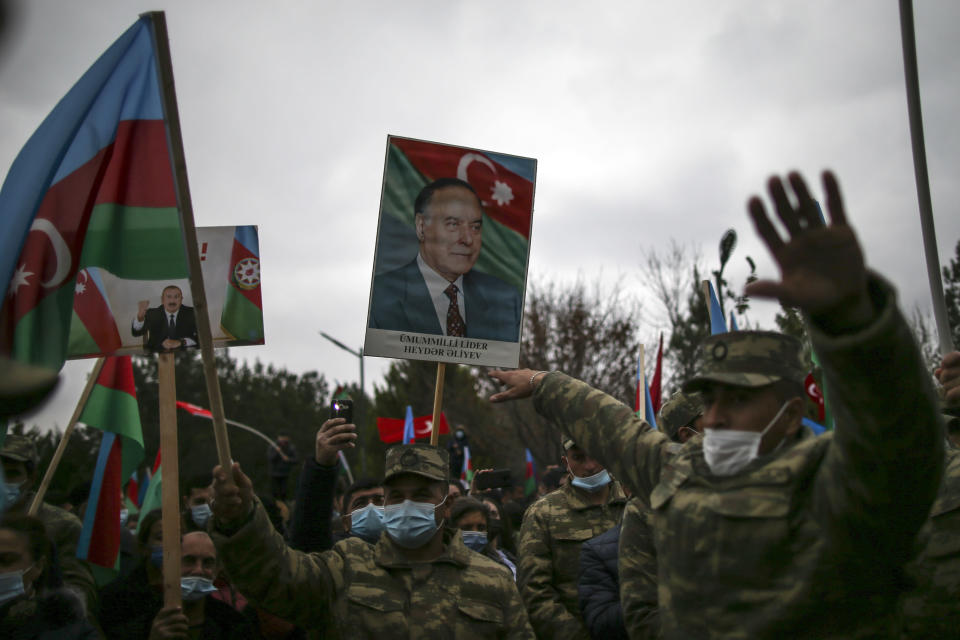 Azerbaijani soldiers hold national flags and portraits of Azerbaijani President Ilham Aliyev, left, and his father and former Azerbaijani President Heydar Aliyev, center, as they celebrate the transfer of the Lachin region to Azerbaijan's control, as part of a peace deal that required Armenian forces to cede the Azerbaijani territories they held outside Nagorno-Karabakh, in Aghjabadi, Azerbaijan, Tuesday, Dec. 1, 2020. Azerbaijan has completed the return of territory ceded by Armenia under a Russia-brokered peace deal that ended six weeks of fierce fighting over Nagorno-Karabakh. Azerbaijani President Ilham Aliyev hailed the restoration of control over the Lachin region and other territories as a historic achievement. (AP Photo/Emrah Gurel