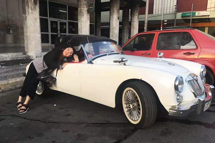 Lulu Yang poses with antique cars on a work trip to Cuba. (Courtesy Lulu Yang)