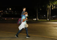 A migrant who aims to reach the U.S. walks along a highway with a child on her shoulders as they leave San Pedro Sula, Honduras with a group before dawn Tuesday, March 30, 2021. (AP Photo/Delmer Martinez)