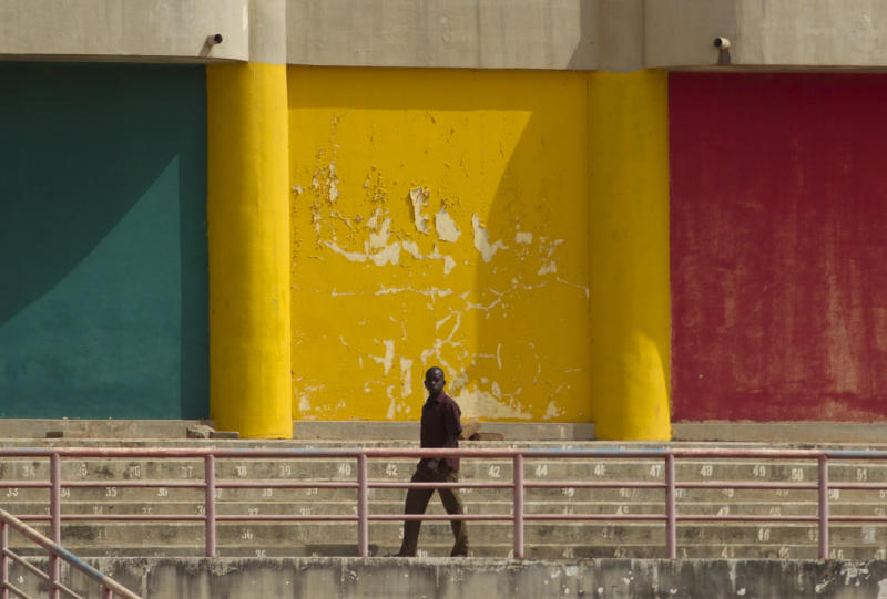 A man walks in front of a wall painted in the colors of the Malian flag, during a rally in support of the ruling military junta attended by roughly one thousand people in a stadium with a capacity of 50,000, in Bamako, Mali Saturday, March 31, 2012. The March 26 stadium is named in commemoration of the date in 1991 when dictator Moussa Traore was overthrown, paving the way for establishment of a democracy which lasted 21 years until mutinous soldiers took power in a coup nine days ago. (AP Photo/Rebecca Blackwell)