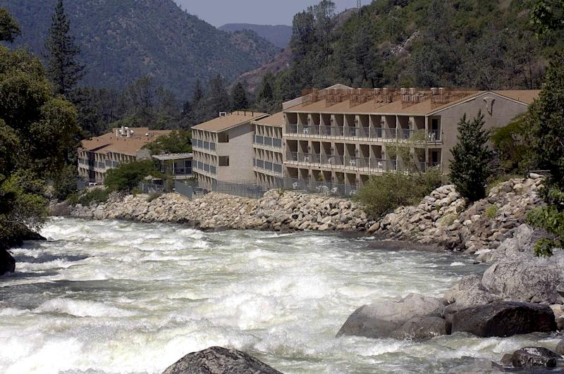 FILE - In this June 9, 2006 file photo, The Yosemite View Lodge on the Merced River remains cut off following a massive rock slide in El Portal, Calif. Almost 800 million tons of rocks and debris tumbled onto Highway 140, creating a blockade that forced tourists from the San Francisco Bay area to take hours-long detours to reach the valley. Some environmentalists now favor digging a tunnel through the still-shifting rubble, although biologists warn that proposal could kill off a rare, native salamander. Other groups are pushing for a broad viaduct to span the river, a solution rafting companies have claimed could cripple their business. And as the state highway repair costs soar up to $180 million dollars in turbulent economic times, many residents are hoping to call the whole thing off. (AP Photo/Al Golub, File)