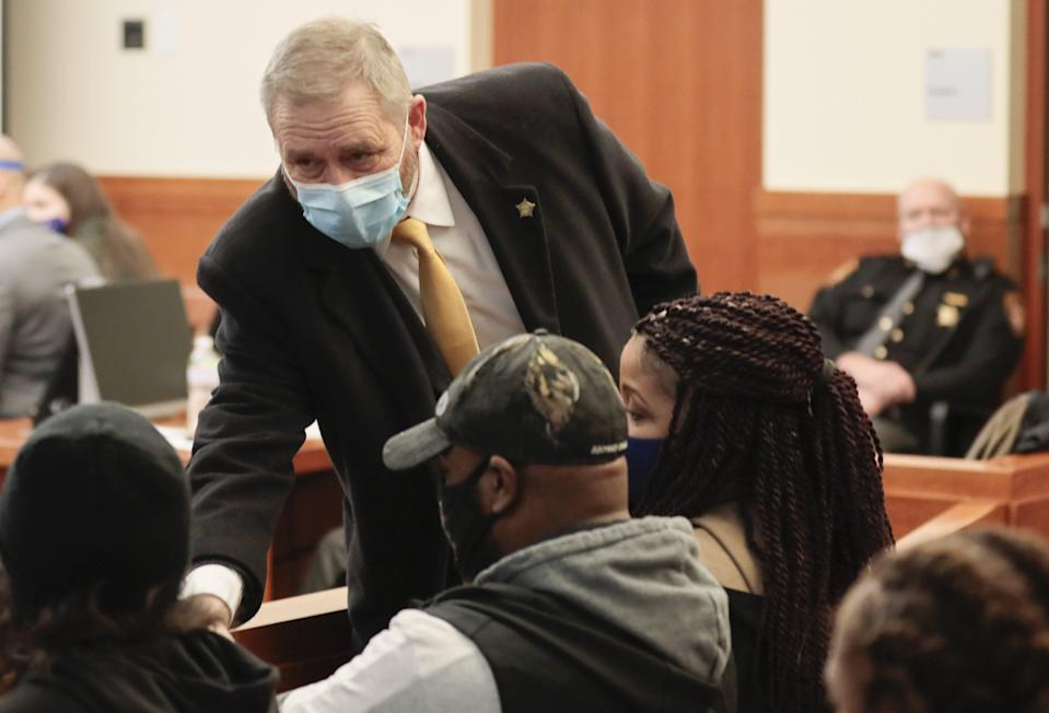 Ohio Attorney General Dave Yost, center, introduces himself to the family of Andre Hill before the start of former Columbus police officer Adam Coy's initial appearance on Friday, Feb. 5, 2021 at the Franklin County Common Pleas Courthouse in Columbus, Ohio. Coy was arraigned on four charges in the December 2020 police shooting death of Andre Hill, a Black man. Coy was charged with one count of murder, one count of felonious assault and two counts of dereliction of duty, one of which was for failure to render aid to Hill after he was shot. His bond was set at $3 million. Yost's office was appointed special prosecutor in the case.