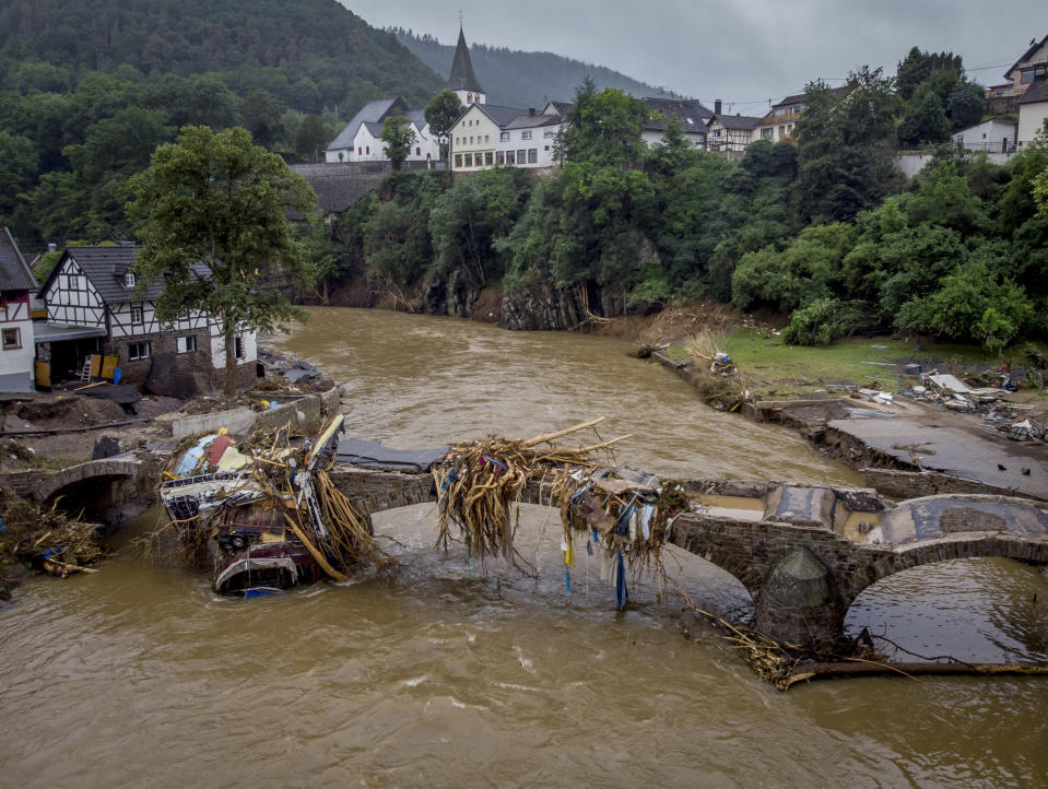 Debris hangs on a damaged bridge over the Ahr river in Schuld, Germany, Friday, July 16, 2021. Two days before the Ahr river went over the banks after strong rain falls causing severals deaths and hundreds of people missing. (AP Photo/Michael Probst)