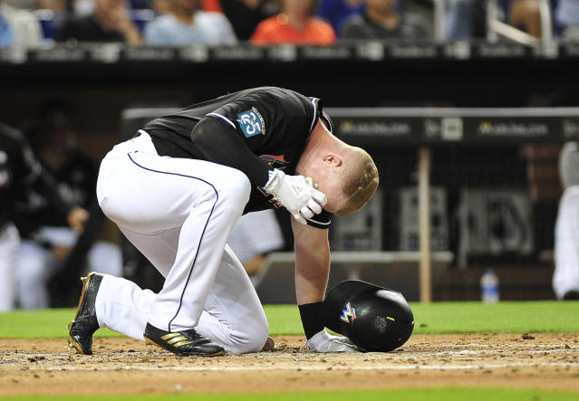 Miami Marlins' Garrett Cooper reacts after being hit by a pitch in the fourth inning of a baseball game against the Chicago Cubs in Miami, Friday, March 30, 2018. (AP Photo/Gaston De Cardenas)