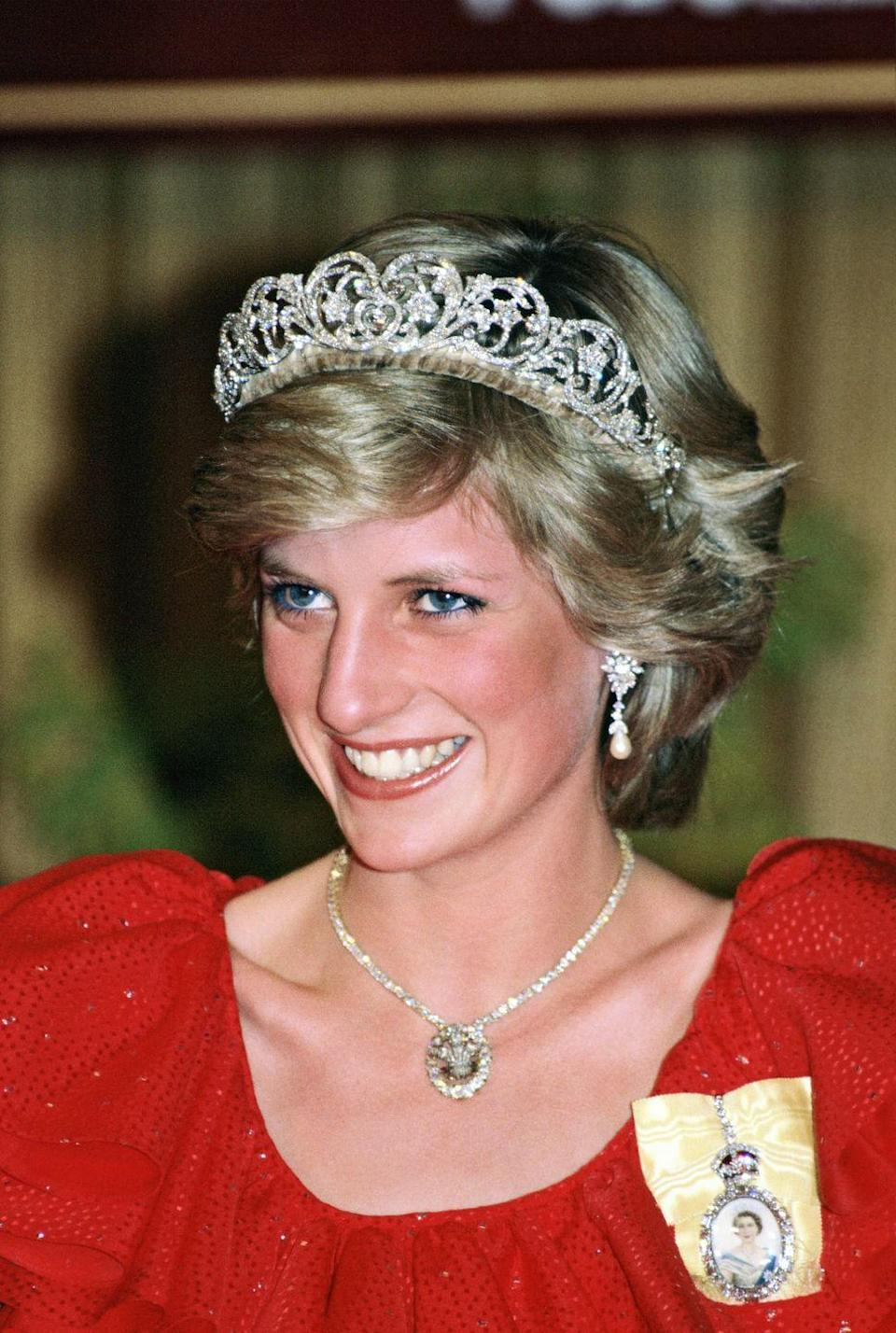 <p>Princess Diana continued to wear the Spencer tiara throughout her life. Here, during an official tour of Australia, she paired it with her Royal Order (in yellow, pinned to her dress). Around Diana's neck is the Prince of Wales Feathers Pendant, a gift to Diana from the Queen Mother to mark her engagement to Prince Charles. The pendant contains 18 brilliant-cut diamonds and tiny emeralds surround the Prince of Wales crest. <br></p>