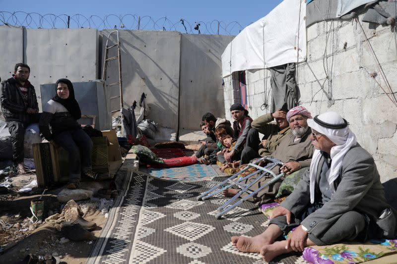 FILE PHOTO: An internally displaced Syrian family sit together outside a tent near the wall in Atmah IDP camp, located near the border with Turkey