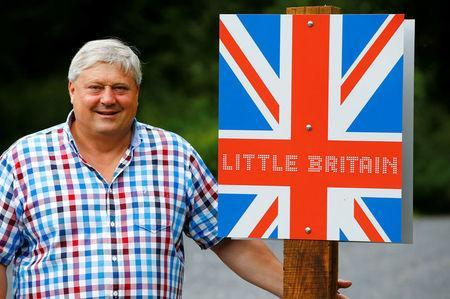 """Gary Blackburn, a 53-year-old tree surgeon and collector of British curiosities from Lincolnshire, Britain, poses in front of a self-made """"Little Britain"""" sign in Linz-Kretzhaus, south of Germany's former capital Bonn, Germany, August 24, 2017. REUTERS/Wolfgang Rattay"""