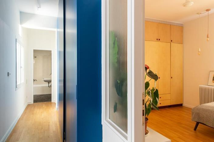 Colbalt blue lines the hallway leading to the bedroom in the Point Supreme-renovated Athens apartment.