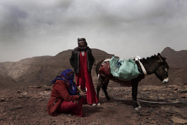 In this March 30, 2019 photo, Umm Yasser, the first Bedouin female guide from the Hamada tribe, looks at Umm Soliman as she plays the flute, near Wadi Sahw, Abu Zenima, in South Sinai, Egypt. Umm Yasser is breaking new ground among the deeply conservative Bedouin of Egypt's Sinai Peninsula. Women among the Bedouin almost never work outside the home, and even more rarely do they interact with outsiders. But Umm Yasser is one of four women from the community who for the first time are working as tour guides. (AP Photo/Nariman El-Mofty)