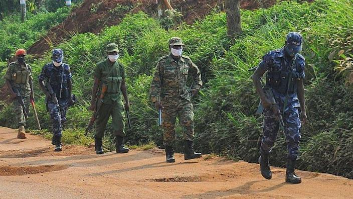Ugandan military forces and police patrol a potholed road in the capital Kampala a day ahead of the presidential elections in Uganda 13 January 2021.