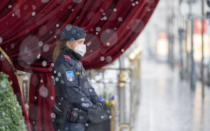 An Austrian police officer stands in front of the Grand Hotel Wien where closed-door nuclear talks with Iran take place in Vienna - AP