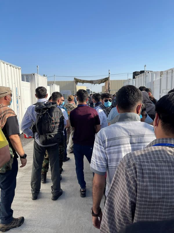 U.S.-trained pilots and other personnel leave camp after being held since fleeing Afghanistan, in Termez