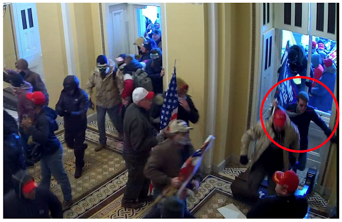 In this image filed with an FBI arrest warrant, a man believed to be Matthew Mark Wood of Reidsville, N.C., storms through a broken window, Trump flag in tow, at the U.S. Capitol in Washington on Jan. 6, 2021.