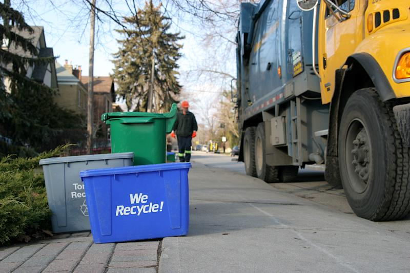 A recycling truck picking up waste.