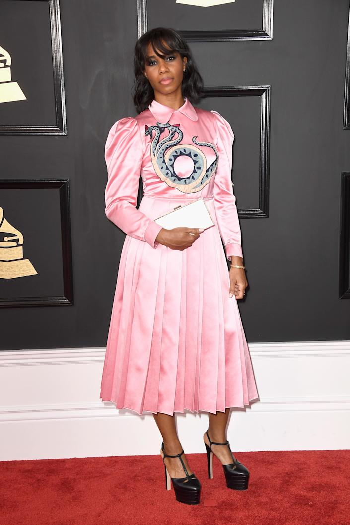 Santigold wearing the #RefreshTheTalk clutch, a high-tech accessory designed to raise awareness for social causes on the red carpet.