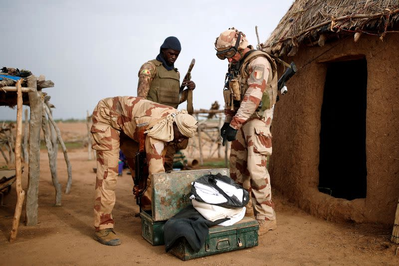 FILE PHOTO: FILE PHOTO: Troops from the Malian Armed Forces (FAMa) and a French soldier conduct a joint patrol during the Operation Barkhane in Ndaki
