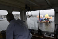 A captain steers his boat around giant balloons depicting U.S. President Joe Biden, left, and British Prime Minister Boris Johnson during a 'crack the crisis' action by NGO's in the harbour of Falmouth, Cornwall, England, during an action by NGO's on Friday, June 11, 2021. (AP Photo/Alberto Pezzali)