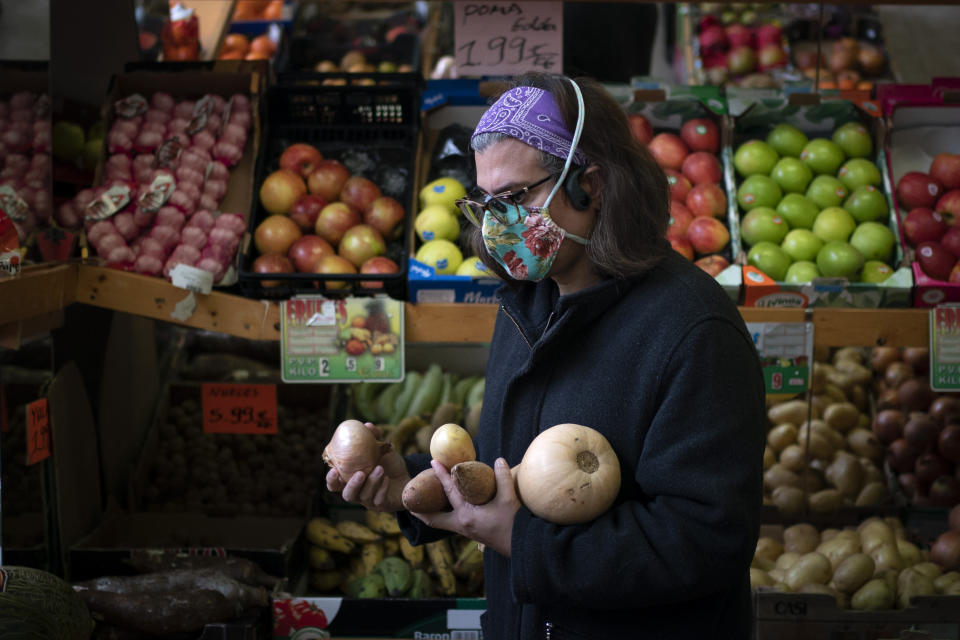"Victoria Martinez, 44, buys vegetables to cook the food for her family at a market in Barcelona, Spain, Monday, Feb. 8, 2021. By May this year, barring any surprises, Martinez will complete a change of both gender and identity at a civil registry in Barcelona, finally closing a patience-wearing chapter that has been stretched during the pandemic. The process, in her own words, has also been ""humiliating."" (AP Photo/Emilio Morenatti)"