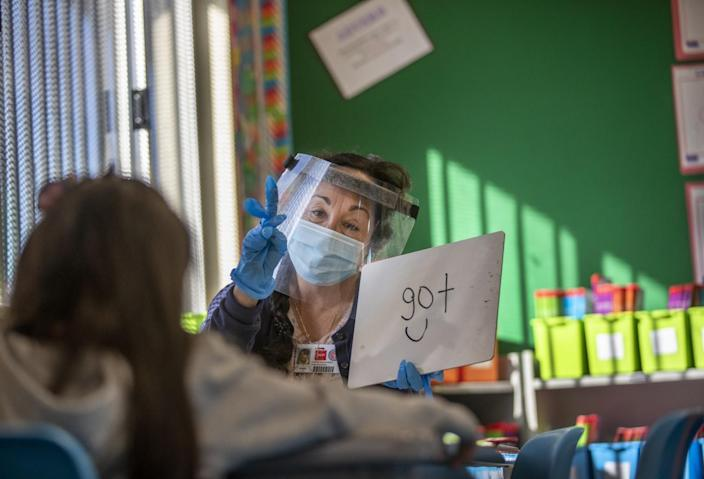 A teacher's aide wearing a face mask and shield gives a lesson