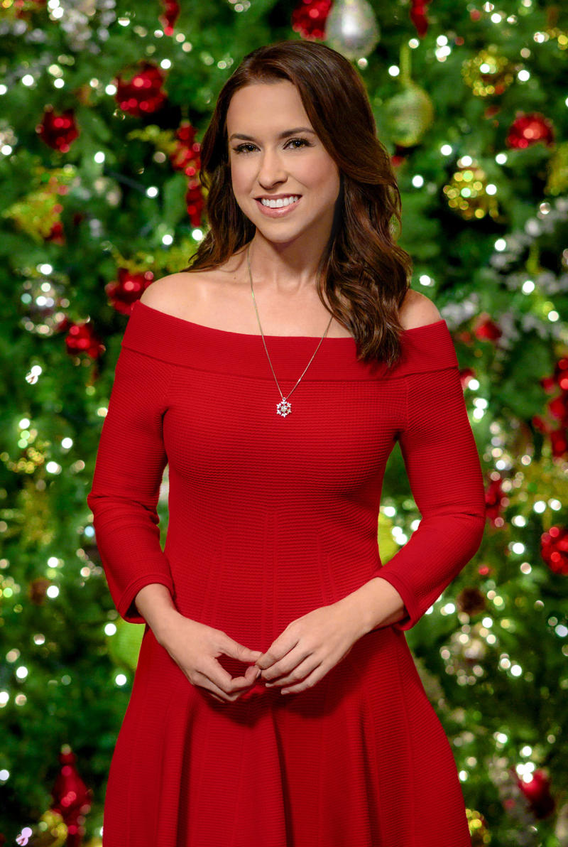 lacey chabert in a red dress in front of a christmas tree