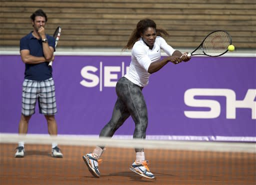 US tennis player Serena Williams, right, hits a ball during a training session as her coach and boyfriend Patrick Mouratouglou looks on, prior to her participation in the Swedish Open Tennis tournament, in Bastad, Sweden, July 14, 2013. (AP Photo/Scanipx Sweden/Peter Widing)