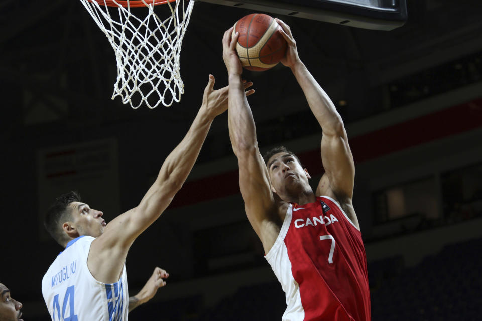 Canada's Dwight Powell drives to the hoop as Greece's Konstantinos Mitoglou tries to defend during the first half of a FIBA men's Olympic qualifying basketball game Tuesday, June 29, 2021 at Memorial Arena in Victoria, British Columbia. (Chad Hipolito/The Canadian Press via AP)
