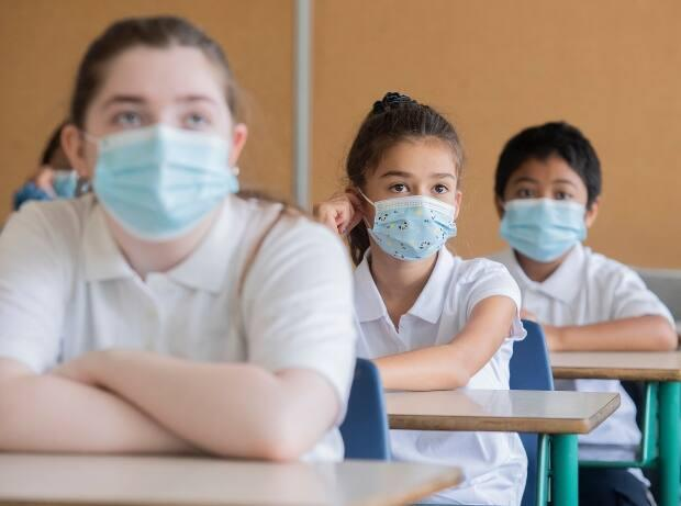 Unvaccinated school-age children who are close contacts to a positive case of COVID-19 don't have to self-isolate,as long as they have no symptoms and wear a face covering, according to the province. (Graham Hughes/The Canadian Press - image credit)