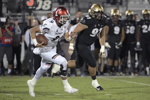 FILE - In this Nov. 17, 2018, file photo, Cincinnati quarterback Desmond Ridder scrambles next to Central Florida defensive lineman Joey Connors (91) during the first half of an NCAA college football game in Orlando, Fla. The Bearcats return most of their key players for a tough schedule that opens with UCLA and Ohio State. (AP Photo/Phelan M. Ebenhack, File)