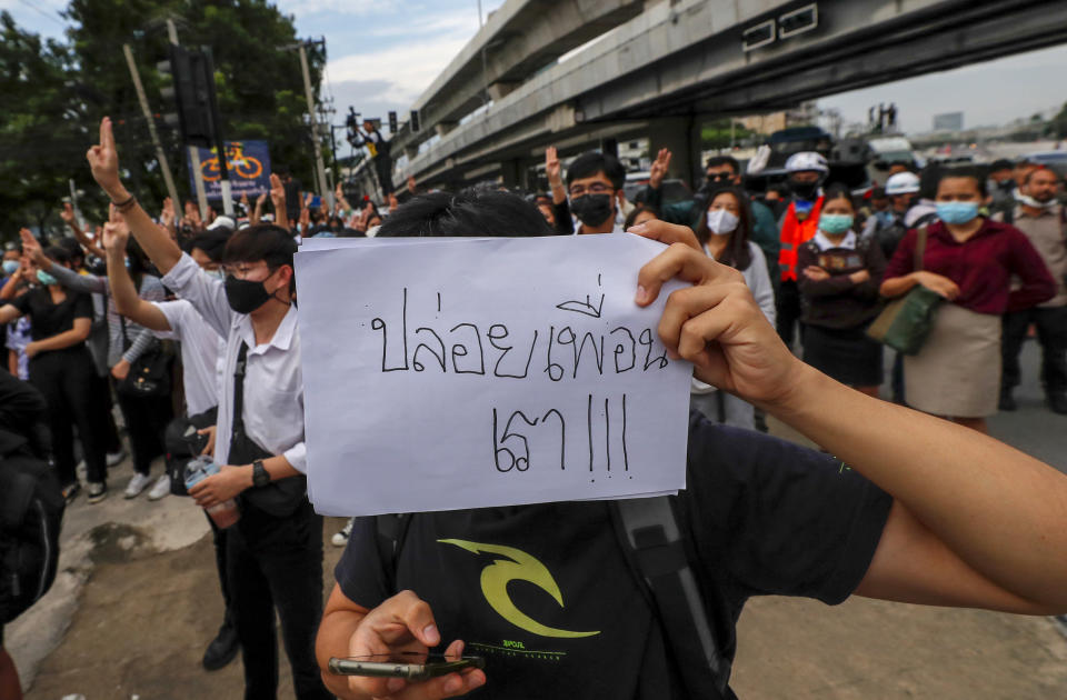 """A pro-democracy activist displays a placard during a demonstration at Kaset intersection, suburbs of Bangkok, Thailand, Monday, Oct. 19, 2020. Thailand's embattled Prime Minister Prayuth Chan-ocha said Monday that there were no plans to extend a state of emergency outside the capital, even as student-led protests calling for him to leave office spread around the country. Placard reads as """"release my friends"""" (AP Photo/Sakchai Lalit)"""