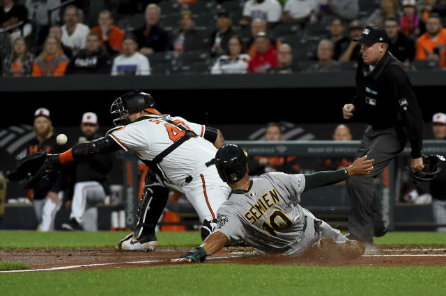 Oakland Athletics Marcus Semien (10) scores next to Baltimore Orioles catcher Jesus Sucre (40) on a double by Matt Chapman during the third inning of a baseball game Wednesday, April 10, 2019, in Baltimore. (AP Photo/Will Newton)