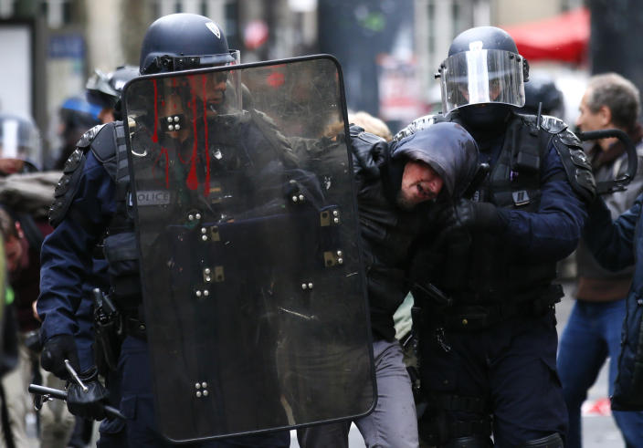 FILE - In this Oct. 10, 2017 file photo, riot police officers detain a demonstrator during a protest in Paris. As videos helped reveal many cases of police brutality, French civil rights activists voiced fears that a new security law would threaten efforts by people from minorities and poor neighborhoods to document incidents involving law enforcement officers. French President Emmanuel Macron's government is pushing a new security bill that would notably make it illegal to publish images of officers with intent to cause them harm. (AP Photo/Francois Mori, File)