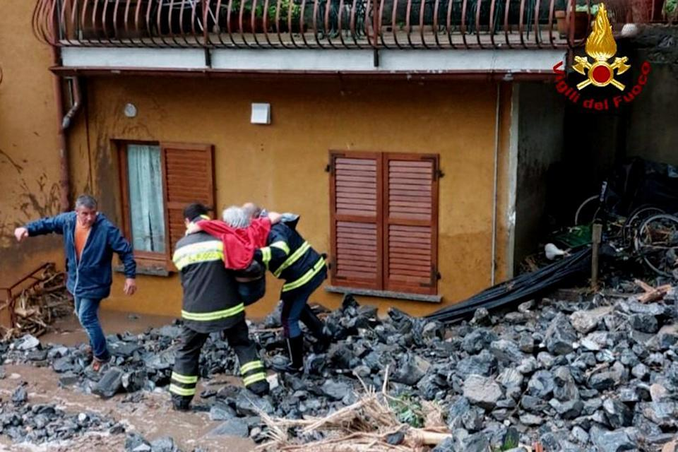 An elderly woman rescued by firefighters from her home  (Vigili del Fuoco via AP)