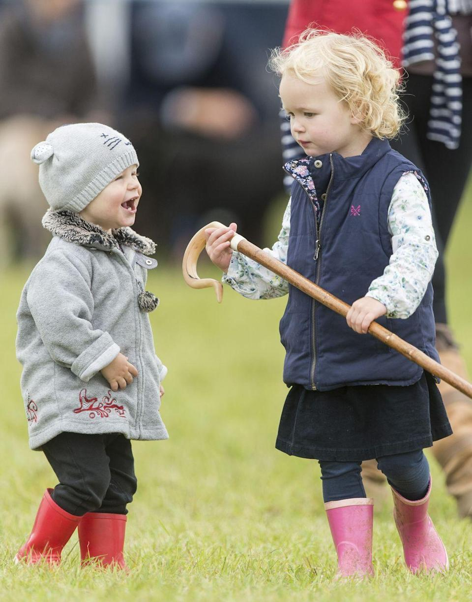 <p>Isla Phillips, nearly 2 years old here, laughs and plays with her older sister, Savannah Phillips, while holding their grandmother Princess Anne's shepherds crook and running around in cute little rain boots with their family dog. </p>