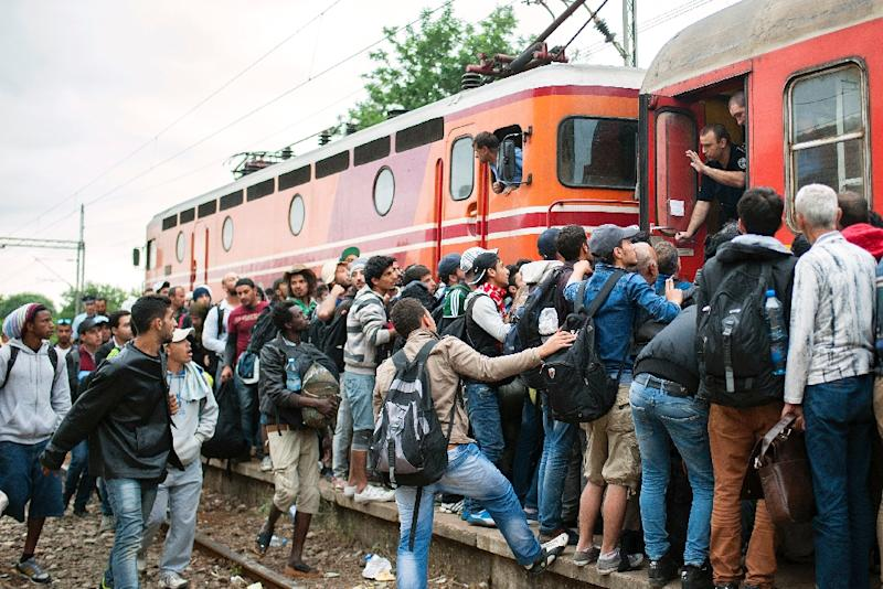 Migrants try to board a train at a station in Demir Kapija, south-eastern Macedonia, on June 18, 2015, on their way to the Serbian border (AFP Photo/Robert Atanasovski)