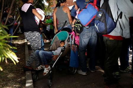 A girl sleeps in a baby stroller next to her mother while they queue to try and buy food outside a supermarket in Caracas, Venezuela March 10, 2017. REUTERS/Carlos Garcia Rawlins
