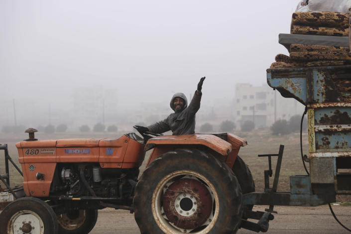 A man waves to a photographer as civilians ride in a truck as they flee Maaret al-Numan, Syria, ahead of a government offensive, Monday, Dec. 23, 2019. (AP Photo/Ghaith al-Sayed)