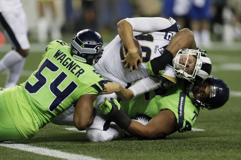 Los Angeles Rams quarterback Jared Goff, center, is tackled by Seattle Seahawks defensive tackle Al Woods, right, and middle linebacker Bobby Wagner. (AP Photo/Stephen Brashear)