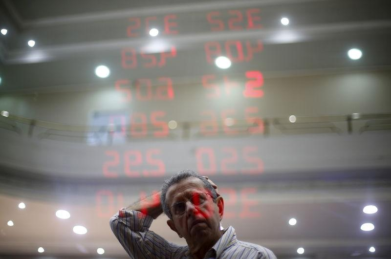 A man reacts as he reads a board showing the Real-U.S. dollar and several foreign currencies exchange rates in Rio de Janeiro