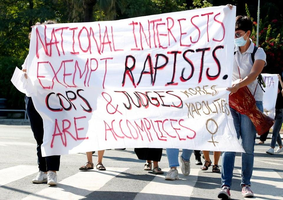 Protesters hold a banner in support of the British woman outside the Supreme Court in Nicosia on Thursday (AP)