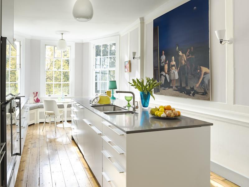 By moving the kitchen to the upper ground floor, overlooking the garden, Irwin has recentered this five-story home. To protect the room's 18th-century paneling, the sleek white Bulthaup cabinets are mounted on a hidden steel frame. The large painting is by Spanish artist Javito Ruiz Perez while the lamp is by MK. The ceiling lights are vintage glass designs, from LASSCO. The vintage chairs are from Howe London; the Saarinen dining table is from Aram.