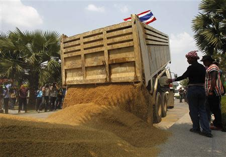 Farmers dump a pile of rice on the ground during a rally demanding the Yingluck administration resolve delays in payment from the rice pledging scheme, outside a Bank for Agriculture and Agricultural Cooperatives in Bangkok March 11, 2014. REUTERS/Chaiwat Subprasom