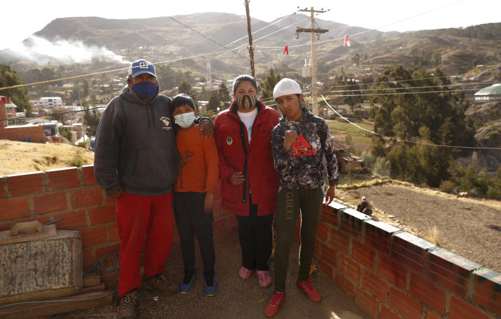 Gracce Kelly Flores, a 12-year-old boxer who goes by the nickname Hands of Stone, right, poses for a photo with her family after her daily boxing workout and breakfast in Palca, Bolivia, early Thursday, June 10, 2021, amid the COVID-19 pandemic. At age 8, Flores defeated a 10-year-old boy, and with three national boxing medals under her belt, she dreams of reaching the women's boxing world championship. (AP Photo/Juan Karita)