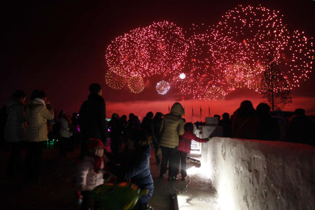 <p>North Koreans watch as fireworks explode as part of New Year celebrations, above the Taedong River as viewed from Kim Il Sung Square, in Pyongyang, North Korea. (Photo: Jon Chol Jin/AP) </p>