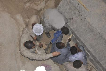 Egyptian excavation workers labor outside the site of the newly discovered giant black sarcophagus in Sidi Gaber district of Alexandria, Egypt July 19, 2018 in this handout picture courtesy of the Ministry of Antiquities. The Ministry of Antiquities/Handout via Reuters